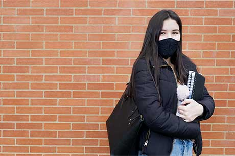 Masked, female student stands agains a brick wall holding a note book and bag.
