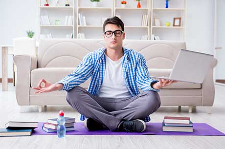 Young man sits in a meditative pose while holding a laptop and surrounded by books.
