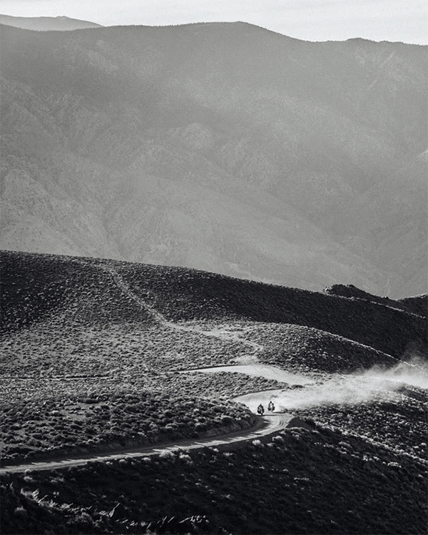Elevatedview of two motorcycles riding along a dusty road in arid hills with mountains in the distance.