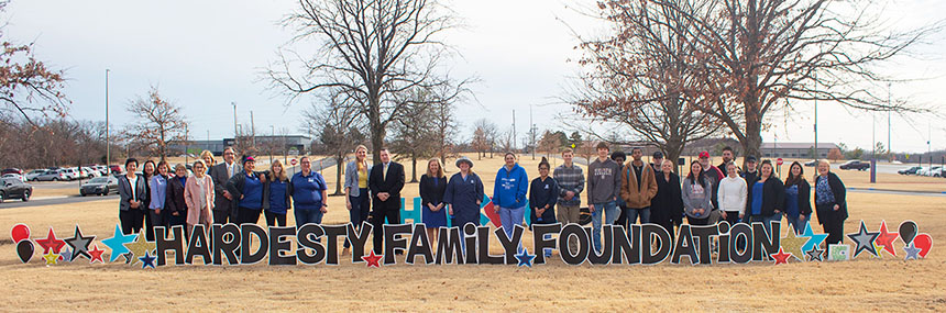 Group of TCC students with the Hardesty Family behind a yard sign that says Hardesty Family Foundation