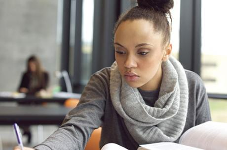 Young female student works diligently at her studies.