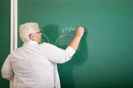 A teacher writes on a chalk board