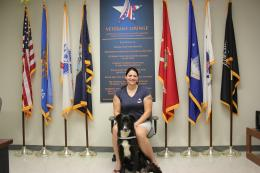 Veterans student with military dog at the Veterans' lounge in front of the US flag and service flags