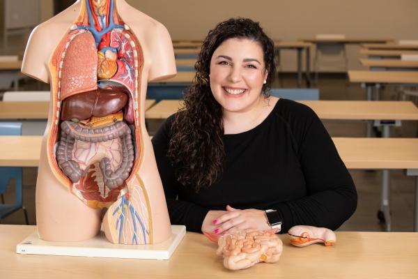 Dr. Leann Fiore in classroom next to anatomy model
