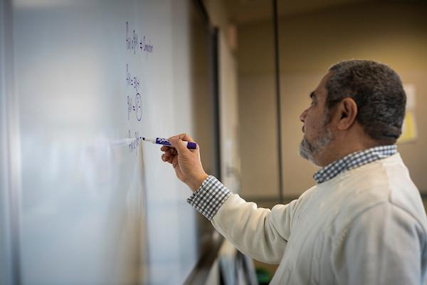 tcc faculty member writing on board in classroom