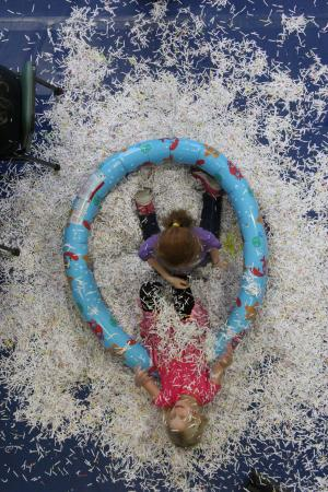 Two kids play in a pool of paper at Family Fun Fair