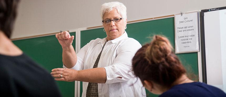 Faculty member teaching students sign language.